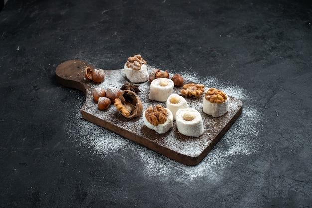 Вид спереди разные печенья с тортами и грецкими орехами на темно-серой поверхности торт бисквитный сахар испечь сладкое печенье Бесплатные Фотографии