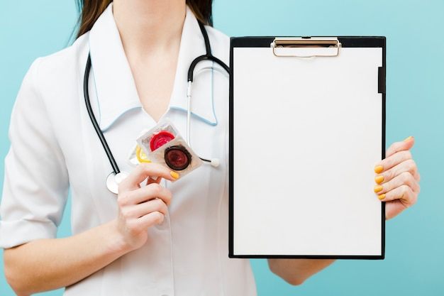 Front view doctor holding condoms and an empty clipboard Free Photo