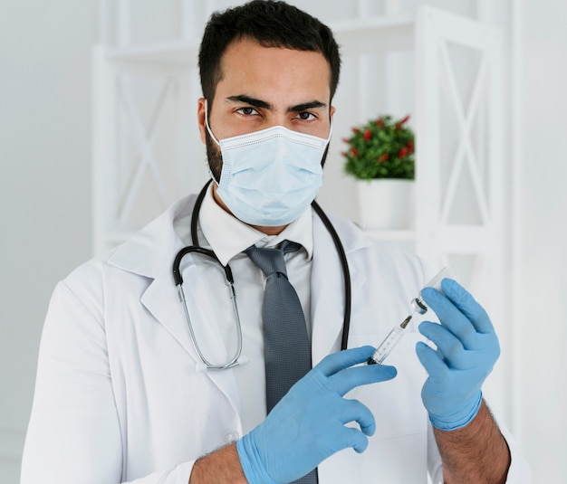 Врач вид спереди с медицинской маской, держащий шприц Бесплатные Фотографии