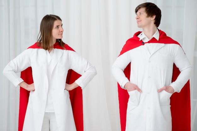 Medici di vista frontale che posano con i cappotti Foto Gratuite