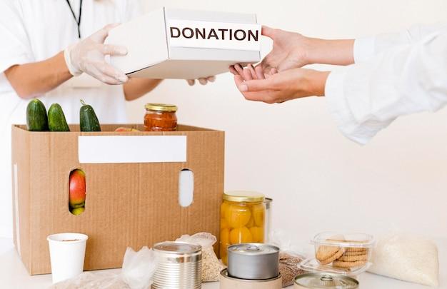 Vista frontale della scatola di donazione in preparazione con il cibo Foto Gratuite