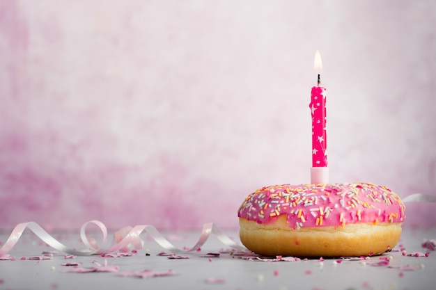 Front view of doughnut with lit candle and copy space Free Photo