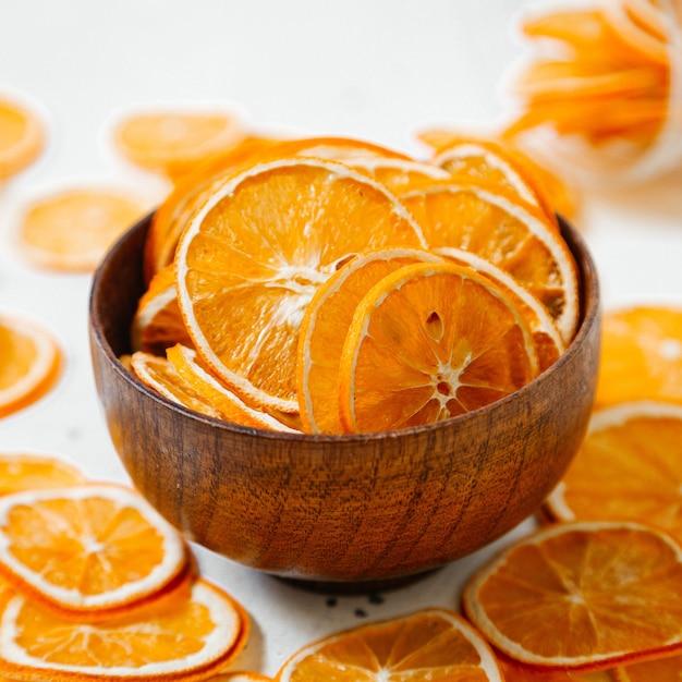 Un'arancia secca vista frontale squilla i dolci all'interno e all'esterno del piccolo piatto sul colore bianco dell'uva passa frutta secca Foto Gratuite