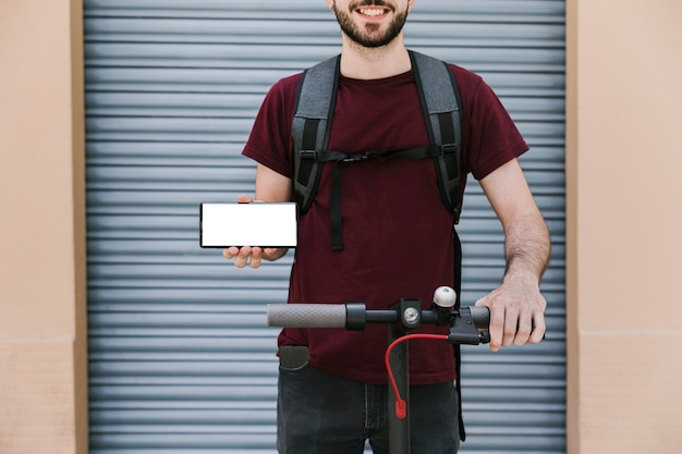 Front view e-scooter rider with mockup smartphone Free Photo