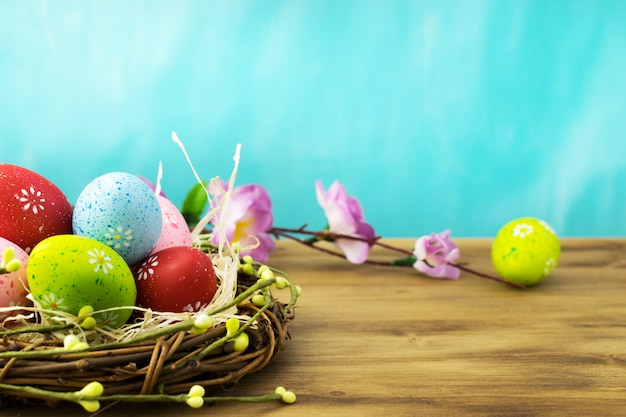 Front view of a easter eggs in nest with  spring flowers branches on brown wood and turqouise background. Premium Photo