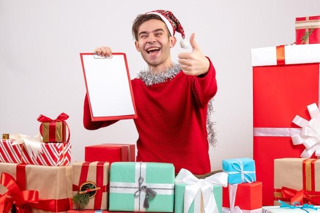 전면보기는 크리스마스 선물 주위에 앉아 젊은 남자를 기뻐 무료 사진