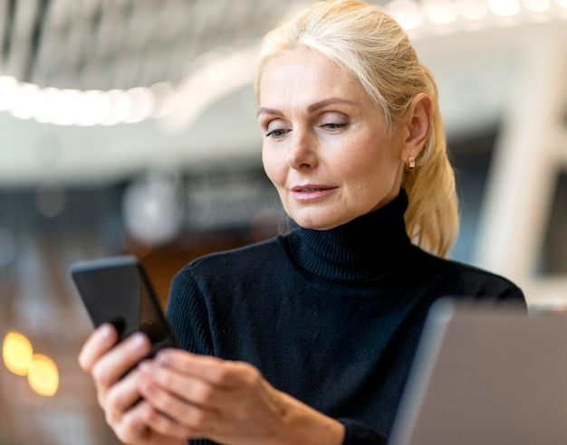 Front view of elder business woman working on laptop and smartphone Free Photo