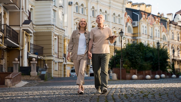 Front view of elder couple out for a walk in the city with tablet Free Photo