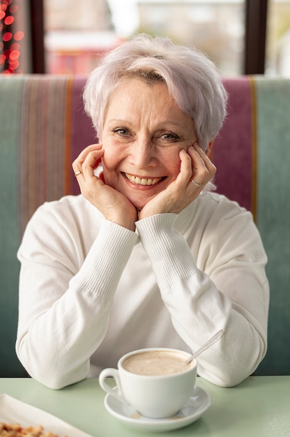 Front view elder smiley woman at restaurant Free Photo