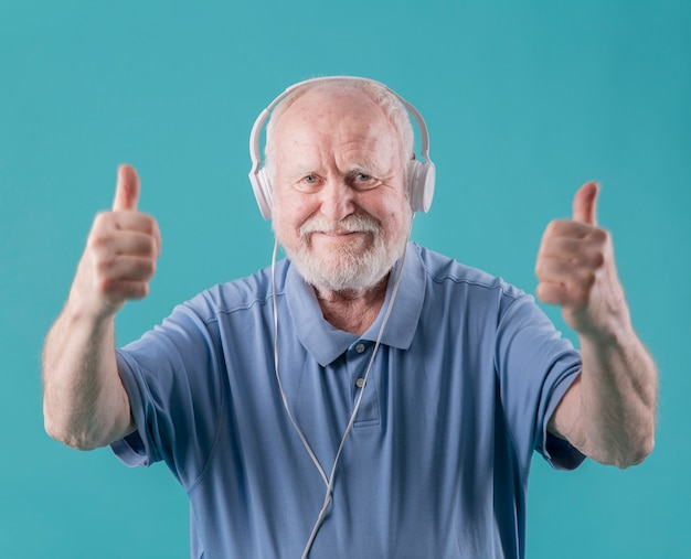 Front view elder with headphones showing ok sign Free Photo