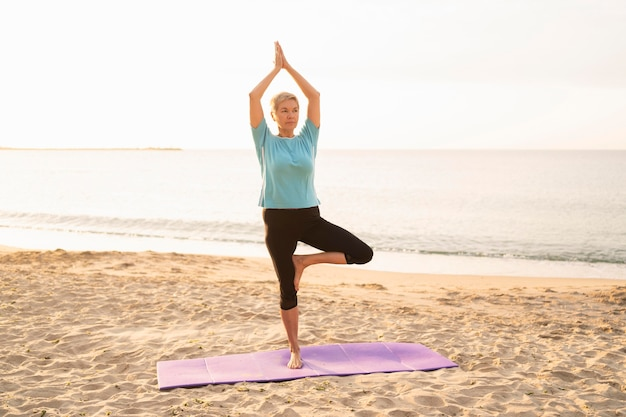 Vista frontale della donna anziana che fa yoga sulla spiaggia Foto Gratuite