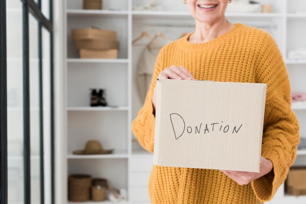Front view of elder woman holding box with donation Free Photo