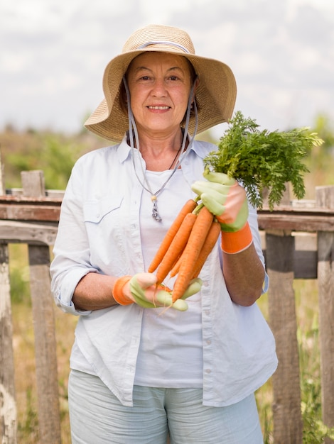 Front view elder woman holding some fresh carrots in her hand Free Photo