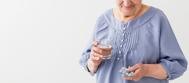 Front view of elder woman taking her pills with copy space Free Photo