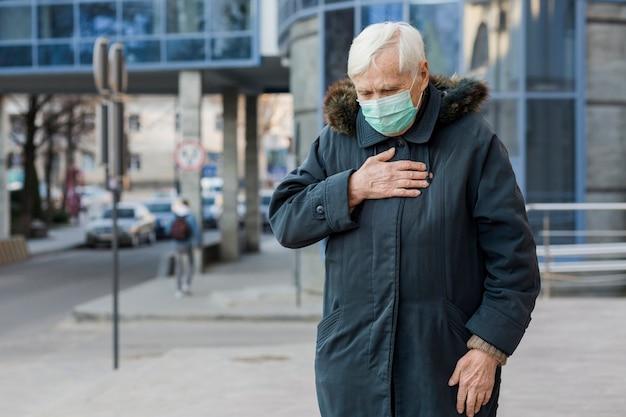 Vista frontale della donna più anziana con la mascherina medica che si sente male mentre nella città Foto Gratuite