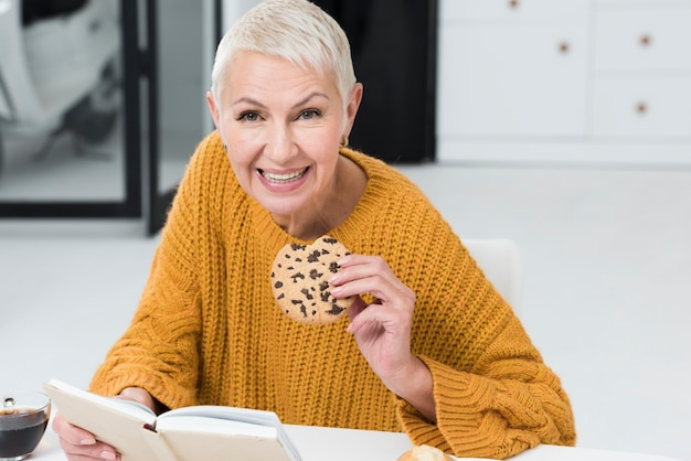 Front view of elderly woman holding big cookie and smiling Free Photo