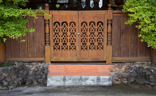 Front view of entrance wood carved door, thai style Premium Photo