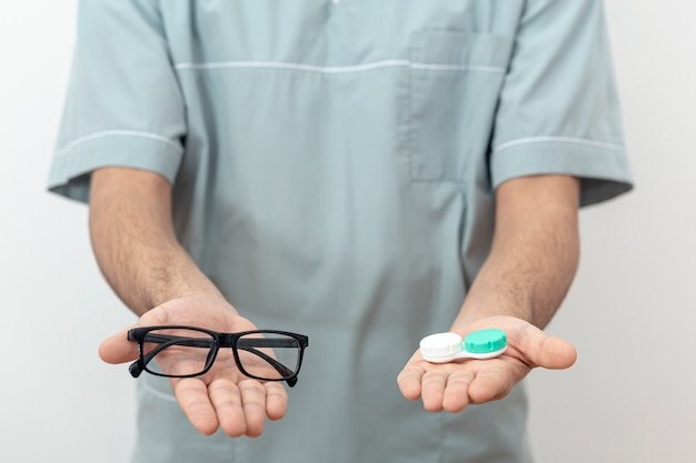Front view of eye specialist holding glasses and contact lenses Free Photo
