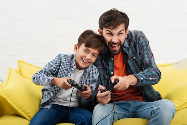 Front view father and son playing on console Free Photo