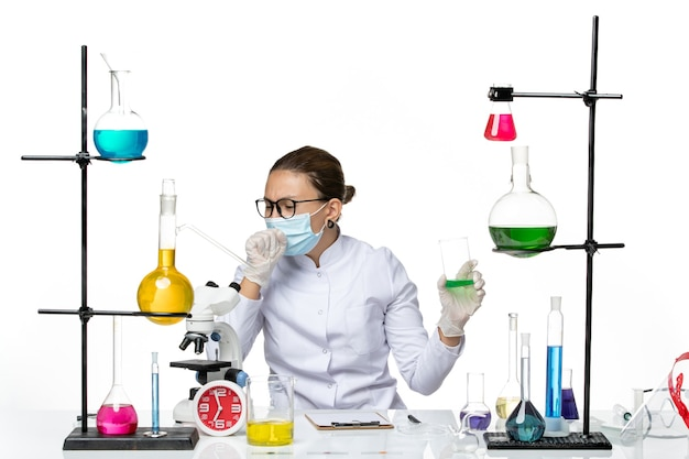 Front view female chemist in medical suit with mask holding solution on white background splash lab virus chemistry covid- Free Photo