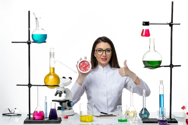 Front view female chemist in white medical suit holding clocks on white desk science virus lab covid pandemic Free Photo