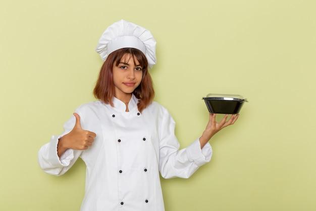 薄緑色の表面にボウルを保持している白いクックスーツの正面図女性料理人 無料写真