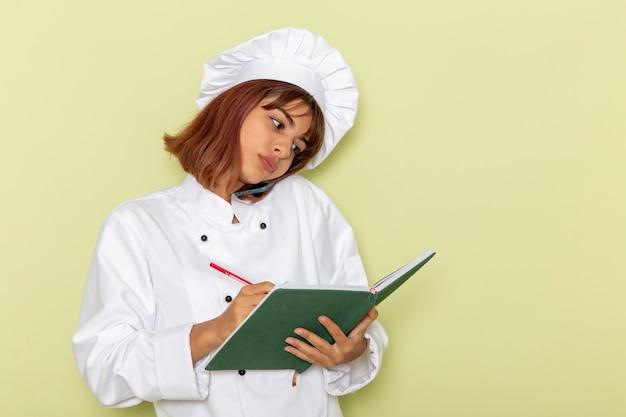 電話で話し、緑の表面にメモを書き留める白いクックスーツの正面図女性料理人 無料写真