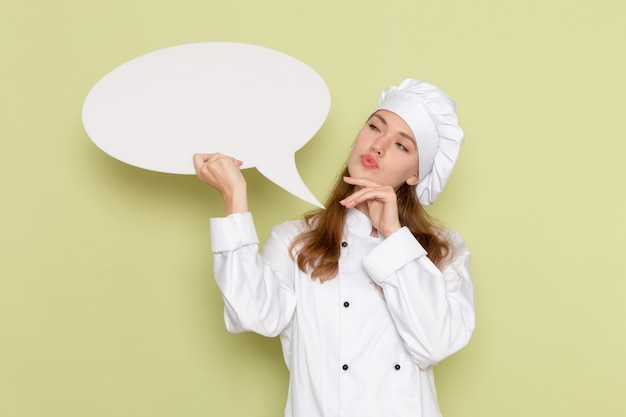 Front view of female cook wearing white cook suit holding big sign and thinking on green wall Free Photo