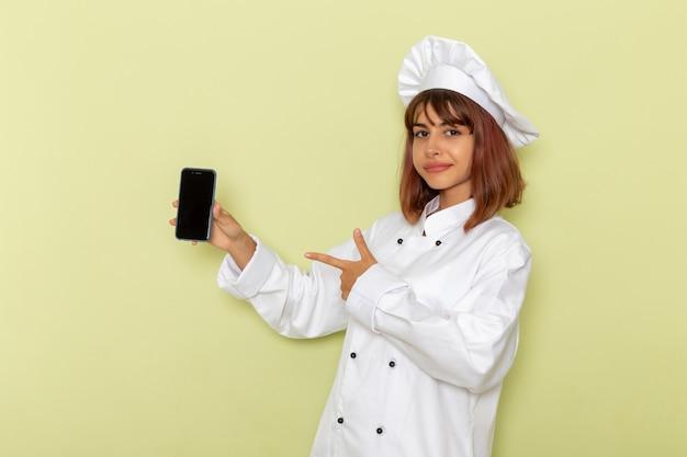 Cuoco femminile di vista frontale in vestito bianco del cuoco che tiene il suo smartphone sulla superficie verde Foto Gratuite