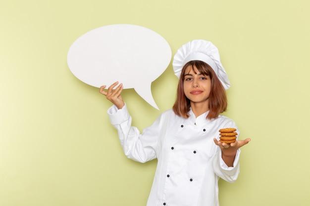 Cuoco femminile di vista frontale in vestito bianco del cuoco che tiene i piccoli biscotti e segno bianco sulla superficie verde Foto Gratuite