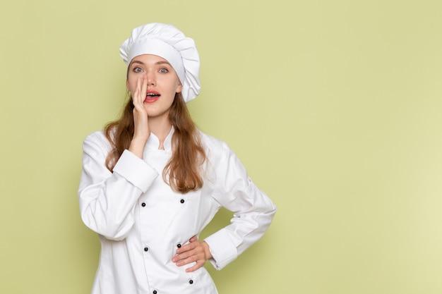 Vista frontale del cuoco femminile in vestito bianco del cuoco che posa e che bisbiglia sulla parete verde Foto Gratuite