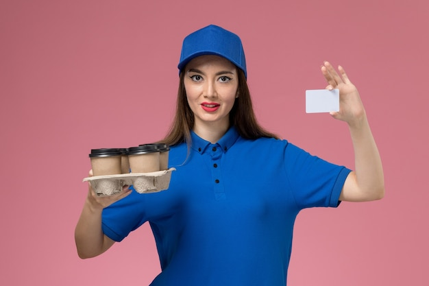 Front view female courier in blue uniform and cape holding coffee cups and white card on pink wall Free Photo