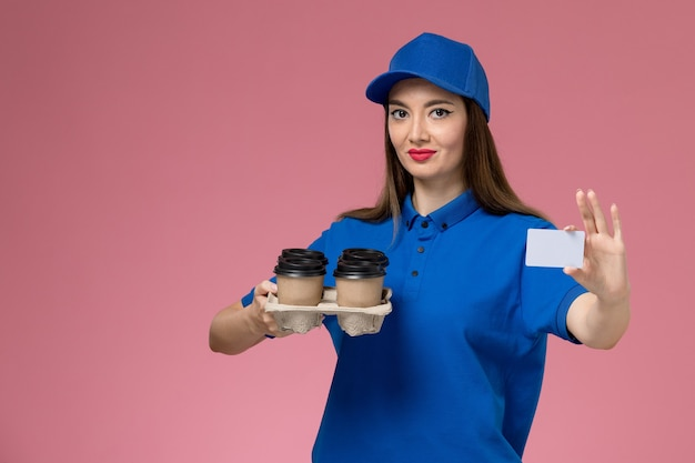 Front view female courier in blue uniform and cape holding coffee cups white card on pink wall Free Photo