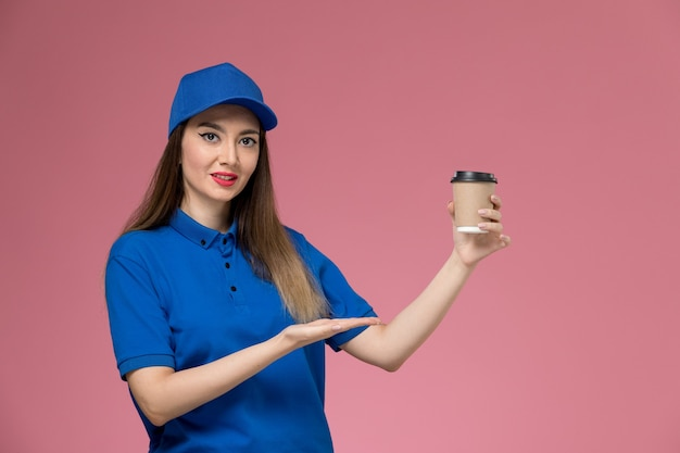 Front view female courier in blue uniform and cape holding delivery coffee cup on the pink wall job worker work Free Photo