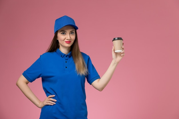 Front view female courier in blue uniform and cape holding delivery coffee cup posing on the pink wall job Free Photo