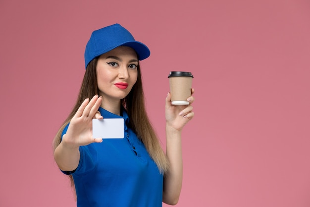 Front view female courier in blue uniform and cape holding delivery coffee cup and white card on pink wall Free Photo