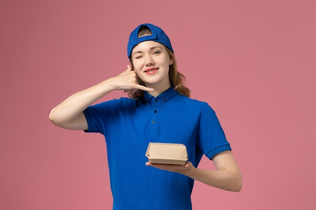 Front view female courier in blue uniform and cape holding little delivery food package on the pink background delivery uniform company work worker girl job Free Photo