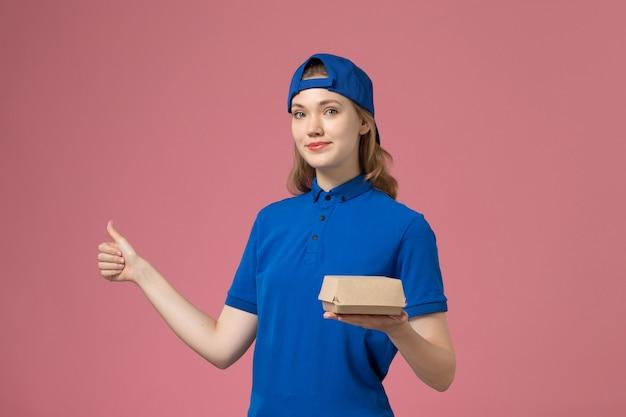 Corriere femminile di vista frontale in uniforme blu e mantello che tiene poco pacchetto di cibo di consegna sul lavoro di lavoro dell'azienda di servizio uniforme di consegna sfondo rosa Foto Gratuite