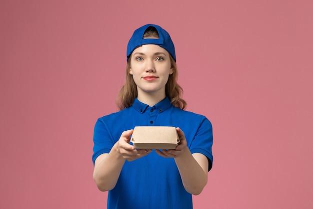 Corriere femminile di vista frontale in uniforme blu e mantello che tiene poco pacchetto di cibo di consegna sullo sfondo rosa uniforme di consegna servizio azienda lavoro lavoratore ragazza lavoro Foto Gratuite