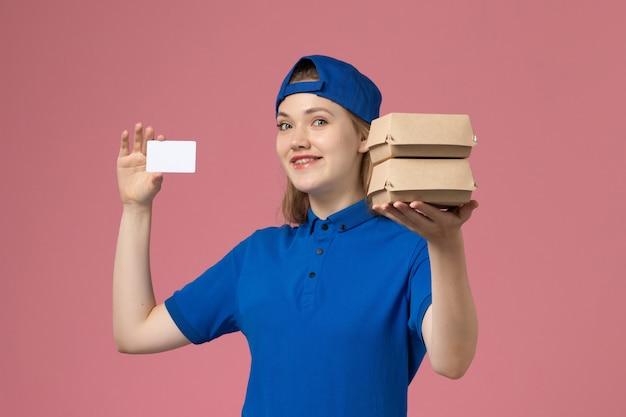 Corriere femminile di vista frontale in capo uniforme blu che tiene piccoli pacchi di cibo di consegna e carta su sfondo rosa lavoratore dipendente consegna servizio Foto Gratuite