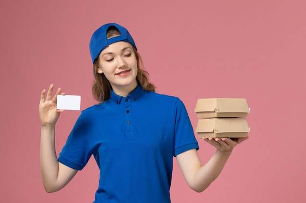 Front view female courier in blue uniform cape holding little delivery food packages and card on pink background service job delivery employee Free Photo