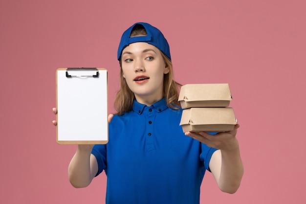 Corriere femminile di vista frontale in capo uniforme blu che tiene piccoli pacchetti di cibo di consegna e blocco note sull'impiegato di servizio di lavoro di consegna sfondo rosa Foto Gratuite