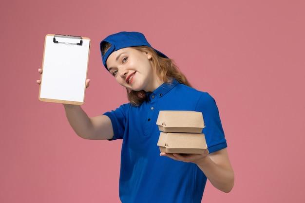Corriere femminile di vista frontale in capo uniforme blu che tiene piccoli pacchetti di cibo di consegna e blocco note su sfondo rosa lavoro dipendente servizio consegna lavoro Foto Gratuite