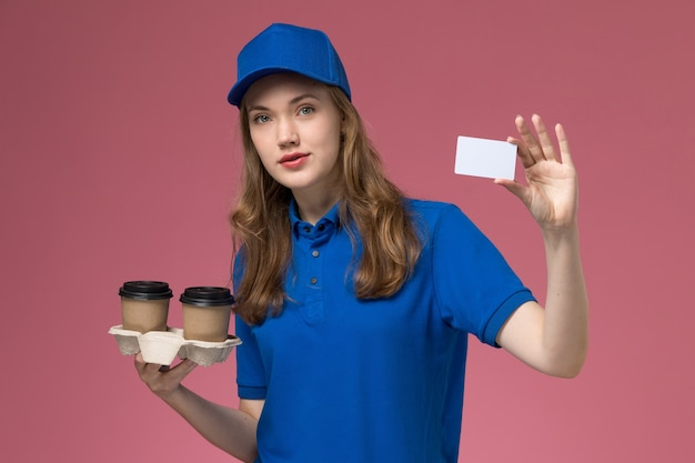 Front view female courier in blue uniform holding brown delivery coffee cups and card on the pink background service uniform delivering company job Free Photo