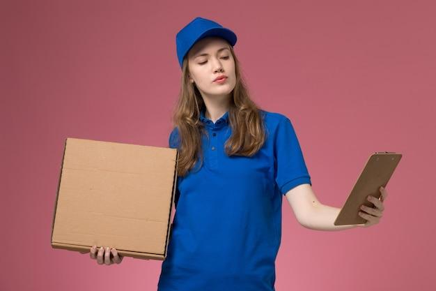 Corriere femminile di vista frontale in uniforme blu che tiene la scatola di consegna del cibo e il blocchetto per appunti sul lavoratore della compagnia di lavoro uniforme di servizio scrivania rosa Foto Gratuite