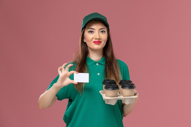 Front view female courier in green uniform and cape holding card and delivery coffee cups on pink wall service uniform delivery job worker Free Photo