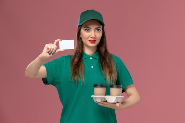 Front view female courier in green uniform and cape holding delivery coffee cups and card on pink wall service job uniform delivery Free Photo
