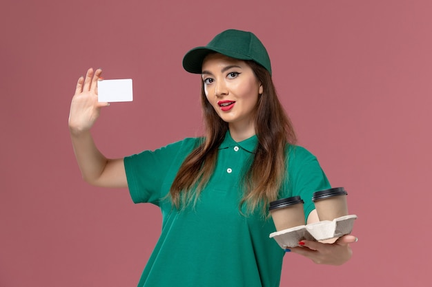 Front view female courier in green uniform and cape holding delivery coffee cups and card on pink wall service job uniform worker delivery Free Photo