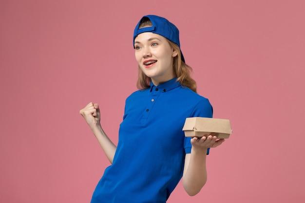青いユニフォームとピンクの背景に小さな配達食品パッケージを保持している岬の正面図女性宅配便仕事配達制服サービス会社の労働者 無料写真