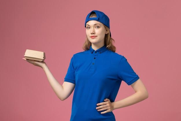 青いユニフォームとピンクの背景に小さな配達食品パッケージを保持している岬の正面図の女性の宅配便仕事配達制服サービスワーカー会社 無料写真